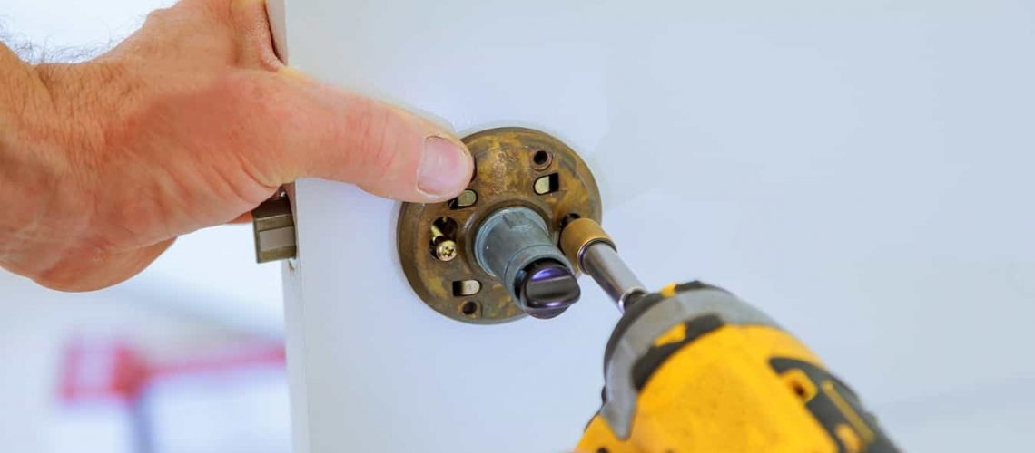 carpenter at lock installation with electric drill into interior wood door