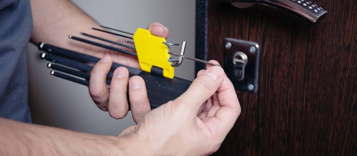 closeup-male-hands-repair-installing-metal-door-lock-with-screwdriver-improved-robbery-protection